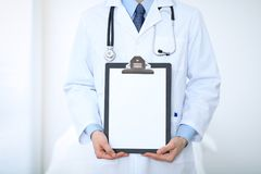 Unknown male doctor standing straight while holding medical clipboard with blank white paper. Medicine and health care Stock Image