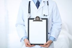 Unknown male doctor standing straight while holding medical clipboard with blank white paper. Medicine and health care Royalty Free Stock Image