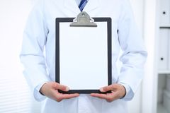 Unknown male doctor standing straight while holding medical clipboard with blank white paper. Medicine and health care Royalty Free Stock Images
