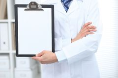 Unknown male doctor standing straight while holding medical clipboard with blank white paper. Medicine and health care Royalty Free Stock Photos