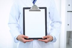 Unknown male doctor standing straight while holding medical clipboard with blank white paper. Medicine and health care Stock Photography