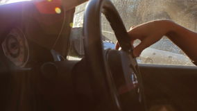 Unknown male driver sitting in the car at parking place. Hand on the steering wheel, sun inside car, window view stock footage