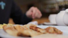 Unknown male person having breakfast in cafe. Unknown man having breakfast in cafe stock video footage