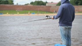 Man is fishing on the river bank. Unknown man in casual clothes is fishing with fishing rod on the river bank against background of blurry brick wall on summer stock video