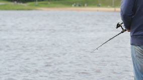 Man is fishing on the river bank. Unknown man in casual clothes is fishing with fishing rod on the river bank against background of blurry brick wall on summer stock footage