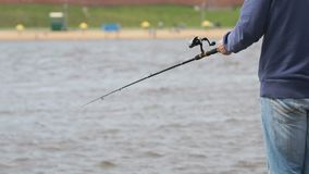 Man is fishing with a rod on background of river stock footage