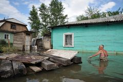 An unknown man on a flooded plot near his house. BARNAUL, RUSSIA - JUNE 26, 2010: An unknown man on a flooded plot near his house. The river Ob, which emerged stock photo