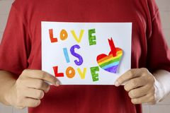Unknown man holding text of love is love. Unknown man holding a paper with text of love is love and heart painted with rainbow colors royalty free stock photo
