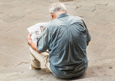 Unknown man is reading news paper. Florence Royalty Free Stock Image