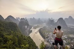 Unknown man takes picture with a mobile phone of Li River view at sunset. Royalty Free Stock Photos