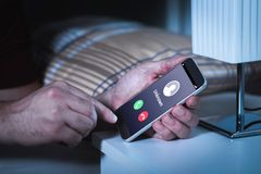 Unknown number calling in the middle of the night. Phone call from stranger. Person holding mobile and smartphone in bedroom bed home late. Unexpected call Royalty Free Stock Images