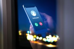 Unknown number calling in the middle of the night. Phone call from stranger. Person holding mobile and smartphone home late royalty free stock photos