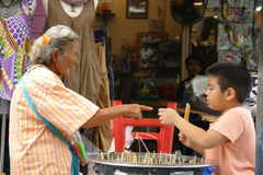 Unknown old woman laughing while selling ice. To a boy at Chatuchak market in Bangkok, Thailand. It was a very hot day stock photography