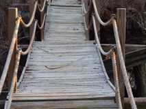 Unknown pathways. A rope railing bridge with weathered wood on a nature trail with sagging planking Stock Images