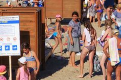 ZELENOGRADSK, KALININGRAD REGION, RUSSIA - JULY 29, 2017: Unknown people standing in queue to dressing-room on a sandy beach. Unknown people standing in queue royalty free stock photos