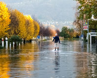 Unknown people surfing on the flooded road Royalty Free Stock Image