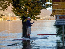Unknown people surfing on the flooded road Royalty Free Stock Photography
