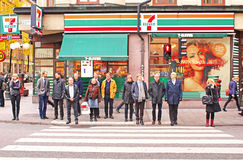 Unknown people are waiting for the green light to go across the road. Behind then shop 7-Eleven. There are 189 7-Elevens in Sweden: most of them in Stockholm Stock Photo
