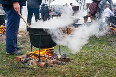 An unknown person prepares a traditional Romanian food prepared at the cauldron on the open fire. Christmas tradition royalty free stock photo