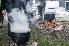 An unknown person prepares a traditional Romanian food prepared at the cauldron on the open fire. Christmas tradition royalty free stock images