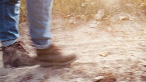Unknown person walking along the dusty road. Foot close up. Unknown person walking along the dusty road. Close up of feet walking on sunset background stock footage