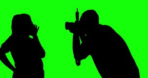 Unknown photographer taking picture of model. Silhouette of unknown photographer taking picture of model in the studio, shot in 4k resolution with green screen stock footage