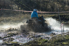 Unknown rider on ATV overcomes a water barrier. Lviv,Ukraine- December 6, 2015: Unknown rider on ATV overcomes a water barrier near Lviv, Ukraine royalty free stock images