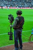 An unknown sports cameraman recording to the competition. Football shooting stock photography
