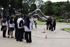 Unknown street artist makes big soap bubbles with two sticks and thread for group of women in Hyde Park. SYDNEY, AUSTRALIA - OCTOBER 28, 2013: An unknown street stock photos