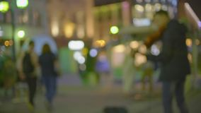 Blurred street musician plays electric violin on illuminated pedestrian street in the evening. Unknown street musician plays electric violin stock footage