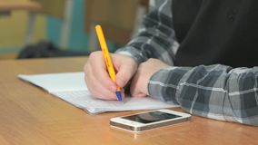 Unknown student writes text using pen in notebook. Close-up of unknown student in grey shirt with black pullover sitting at desk at lesson at university writes stock video footage