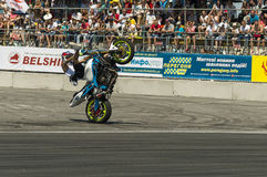 Unknown stunt biker entertain the audience. LLviv, Ukraine - June 7, 2015: Unknown stunt bikers  entertain the audience before the start of the championship of Royalty Free Stock Images