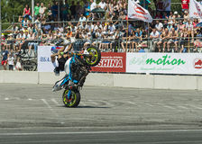 Unknown stunt biker entertain the audience. LLviv, Ukraine - June 7, 2015: Unknown stunt bikers  entertain the audience before the start of the championship of Royalty Free Stock Photos