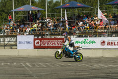 Unknown stunt biker entertain the audience. Lviv, Ukraine - June 7, 2015: Unknown stunt biker entertain the audience before the start of the championship of Royalty Free Stock Photography