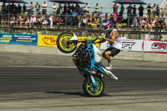 Unknown stunt biker entertain the audience. Lviv, Ukraine - June 7, 2015: Unknown stunt biker entertain the audience before the start of the championship of Stock Photos