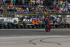 Unknown stunt biker entertain the audience. Lviv, Ukraine - June 7, 2015: Unknown stunt biker entertain the audience before the start of the championship of Royalty Free Stock Images