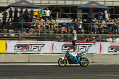 Unknown stunt biker entertain the audience. Lviv, Ukraine - June 7, 2015: Unknown stunt biker entertain the audience before the start of the championship of Royalty Free Stock Photos