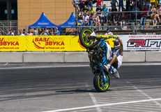 Unknown stunt biker entertain the audience. Lviv, Ukraine - June 7, 2015: Unknown stunt biker entertain the audience before the start of the championship of Royalty Free Stock Image