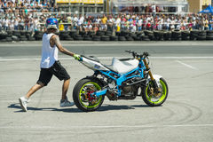 Unknown stunt biker entertain the audience. Lviv, Ukraine - June 6, 2015: Unknown stunt biker entertain the audience before the start of the championship of Royalty Free Stock Photo