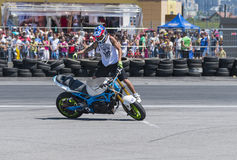Unknown stunt biker entertain the audience. Lviv, Ukraine - June 6, 2015: Unknown stunt biker entertain the audience before the start of the championship of Stock Photos