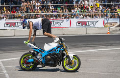 Unknown stunt biker entertain the audience. Lviv, Ukraine - June 6, 2015: Unknown stunt biker entertain the audience before the start of the championship of Royalty Free Stock Image