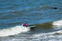 ZELENOGRADSK, KALININGRAD REGION, RUSSIA - JULY 29, 2017: Unknown surfer resting and having of surf on the blue waves. Unknown surfer resting and having of surf Royalty Free Stock Photos