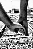 Into The Unknown Together. A dramatic photograph of a couple holding hands while walking along the railroad tracks Stock Image