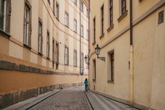 Tourist girl in green jacket walks along beautiful deserted narrow street in Prague between two historic buildings Royalty Free Stock Images