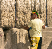 Unknown tourist in yellow  shorts and a bright colored bandana on his head lays down a note into a crack in the Western Wall Royalty Free Stock Images