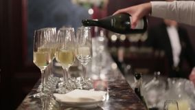 Unknown waiter is pouring champagne into glasses on the bar back. Luxury restaurant or hotel. Wedding and birthday stock video