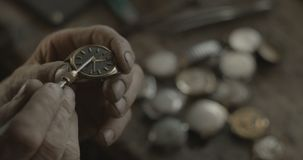 The unknown watchmaker is fixing the ancient vintage hand watch in his workshop. No face. 4k. RED camera shot. stock images