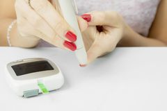 Unknown woman checking blood sugar. Closeup of unknown woman using lancet pen while checking blood sugar with glucometer Stock Image