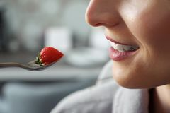 Unknown woman eating strawberry and smiling stock photography