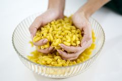 Unknown woman hands hold raw macaroni Stock Images